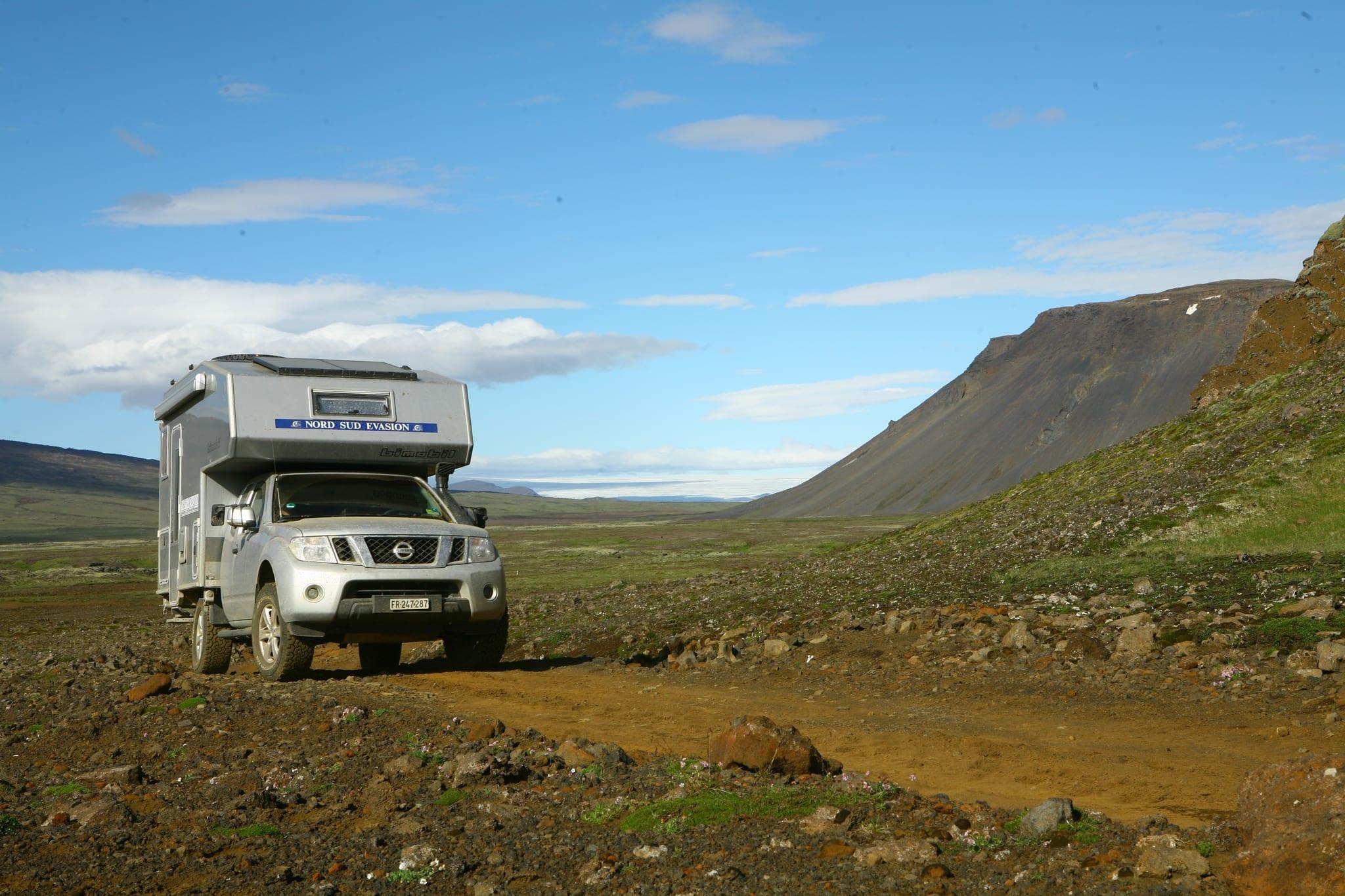 4x4 Camper sur une piste ocre dans un paysage volcanique pendant le raid campers tour Askja en Islande, juillet 2020