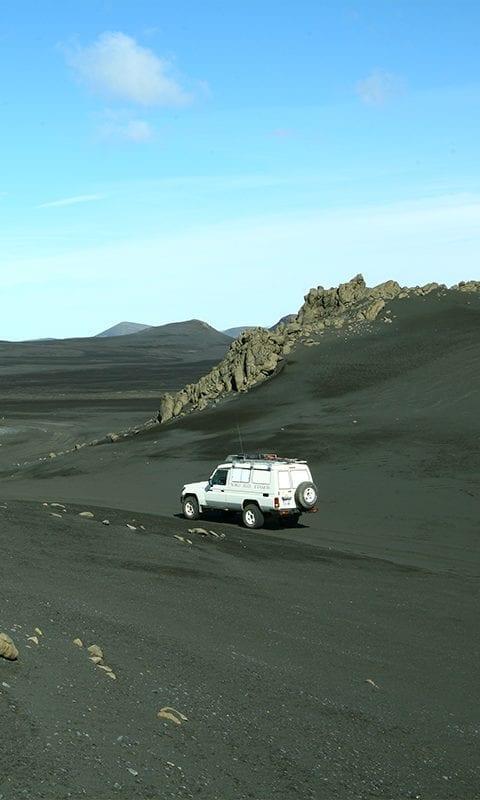 4x4 blanc dans un superbe défilé rocheux dans le sable noir pendant le raid 4x4 hekla Islande, juillet 2020