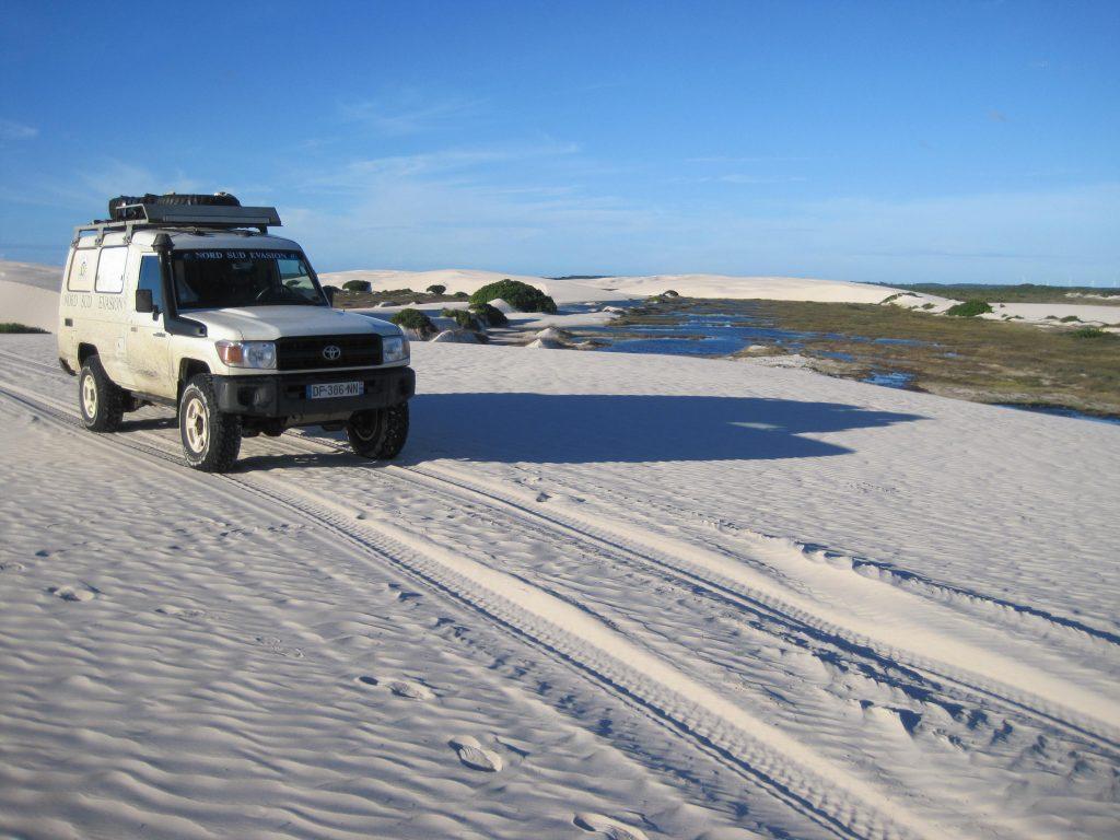 4x4 devant lac turquoise dans les dunes blanches des Lançois de Maranhenses au Brésil pendant le raid 4x4 Giga-raid cayenne ushuaia en amérique du sud, février 2020