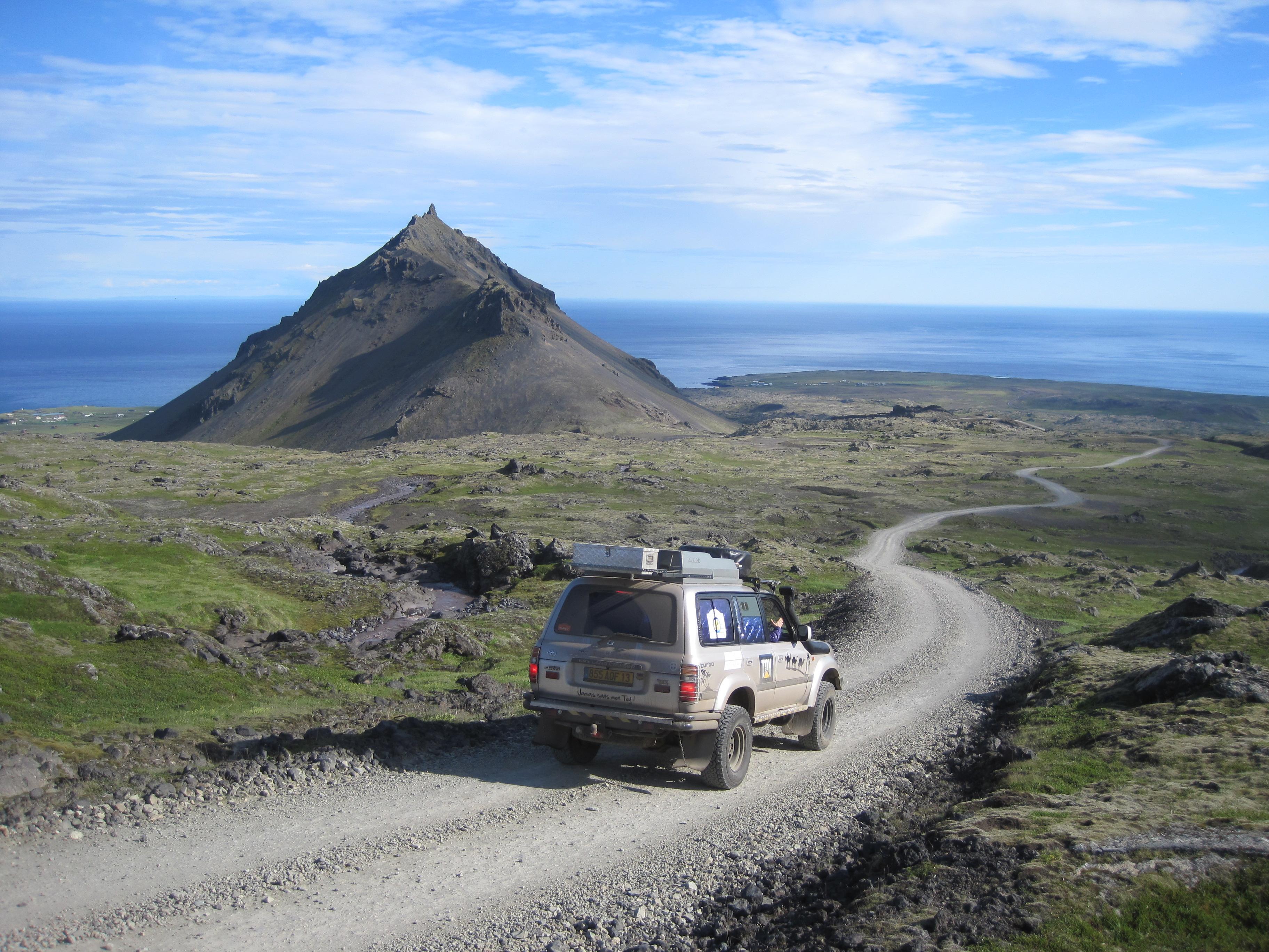 4x4 sur une piste gravillonnée allant vers la mer au soleil pendant le raid 4x4 Hekla Islande, Mai 2020