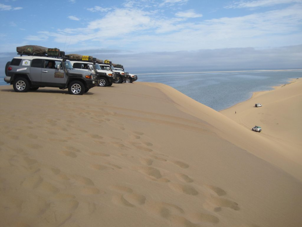 Plusieurs 4x4 Toyota FJ cruiser sur une dune du Namib près de l'océan pendant le raid 4x4 Himbas Dunes Namibie, déc 2019